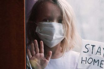 a child with a mask looks out of window with a stay home message